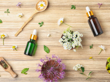 Flat lay composition with essential oils and flowers on wooden table